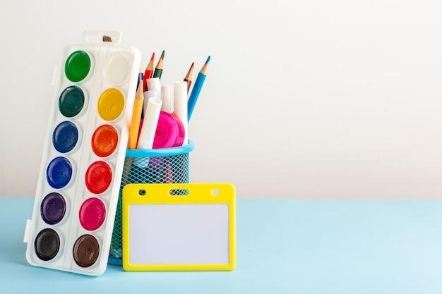 Vista frontal de diferentes lápis coloridos com tintas na mesa azul