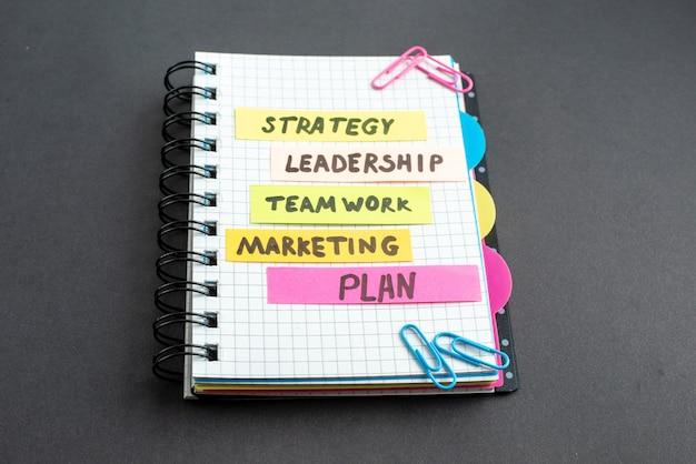 Vista frontal de diferentes notas de negócios no bloco de notas em fundo escuro
