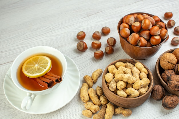 Vista frontal de diferentes nozes, amendoins, avelãs e nozes com uma xícara de chá na superfície branca