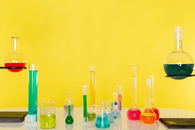 Vista frontal de diferentes soluções coloridas dentro de frascos em cima da mesa