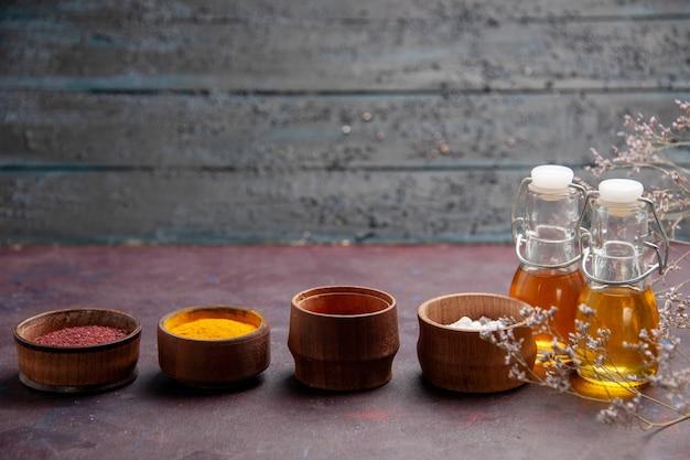 Vista frontal de diferentes temperos com azeite de oliva na mesa escura