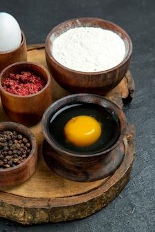 Vista frontal de diferentes temperos com farinha e ovo no espaço cinza