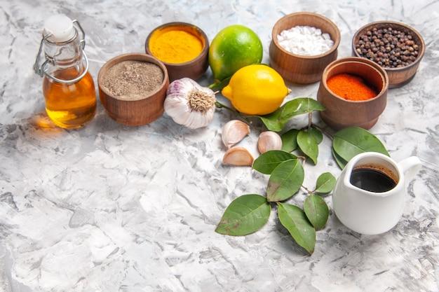Vista frontal de diferentes temperos com limão e alho no piso branco óleo picante sal de frutas