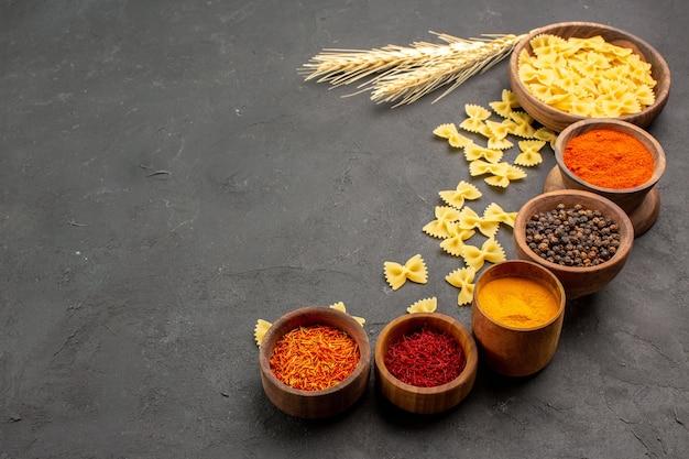 Vista frontal de diferentes temperos com massa crua na mesa escura especiarias pimenta picante muitas massas