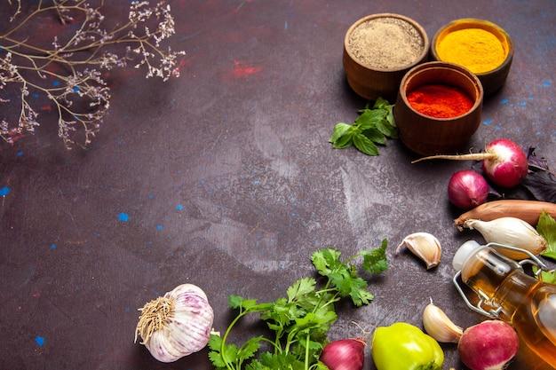 Vista frontal de diferentes temperos com verduras e vegetais no espaço escuro