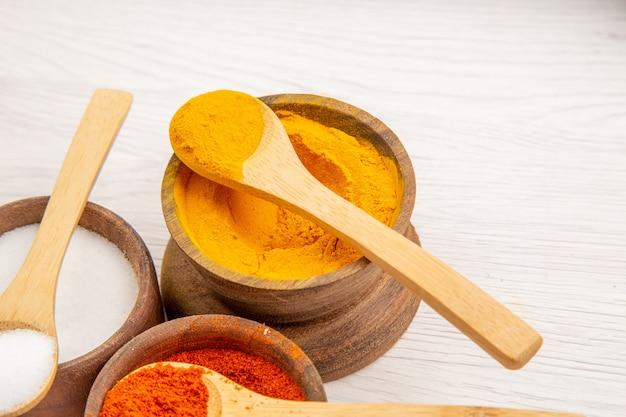 Vista frontal de diferentes temperos dentro de pequenos potes na mesa branca pimenta cor de comida picante
