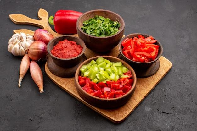 Vista frontal de diferentes vegetais com verduras em fundo cinza salada refeição saúde madura picante