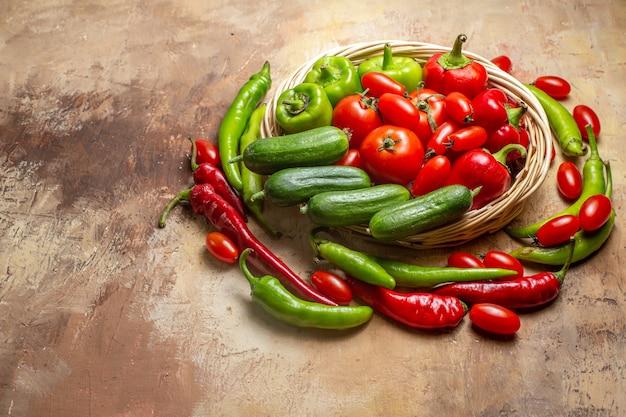 Vista frontal de diferentes vegetais em uma cesta de vime cercada por pimentas e tomates cereja em fundo âmbar