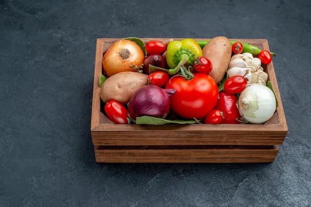 Vista frontal de diferentes vegetais frescos na mesa escura de vegetais frescos salada madura