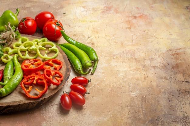 Vista frontal de diferentes vegetais, pimentas picantes, pimentões cortados em pedaços na tábua redonda de madeira, tomates cereja, pimentões, fundo amarelo ocre