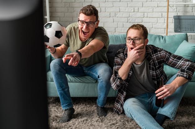 Vista frontal de dois alegres amigos do sexo masculino assistindo esportes na tv juntos e segurando uma bola de futebol