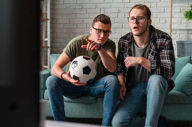 Vista frontal de dois amigos do sexo masculino assistindo esportes na tv juntos e segurando futebol