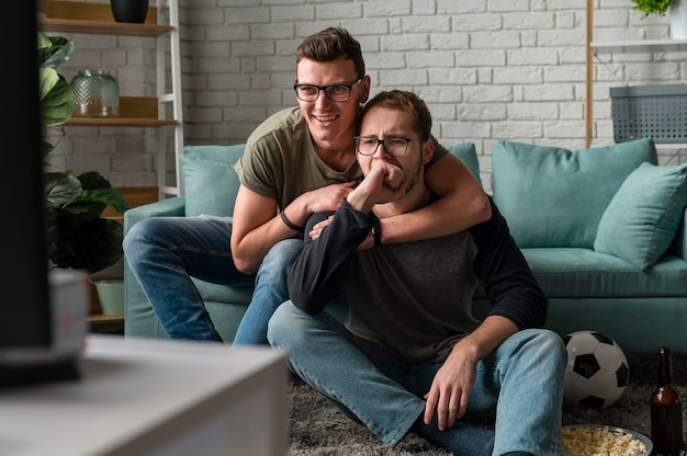 Vista frontal de dois amigos do sexo masculino assistindo esportes na tv juntos
