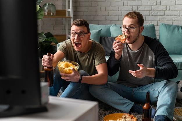 Vista frontal de dois amigos do sexo masculino tomando cerveja com pizza e assistindo esportes na tv