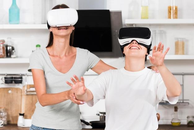 Vista frontal de dois amigos em casa se divertindo com fone de ouvido de realidade virtual