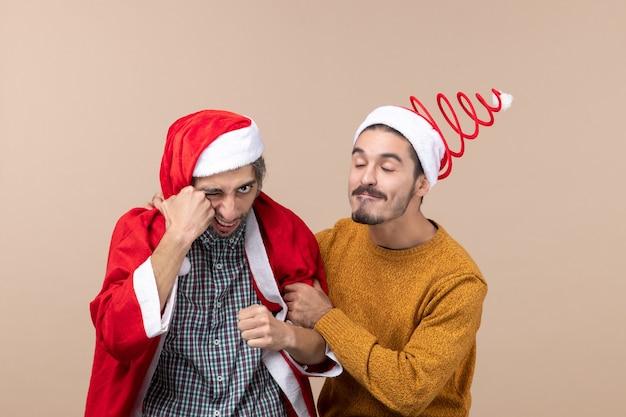 Vista frontal de dois amigos, um com casaco de papai noel dando um soco em si mesmo e o outro segurando o braço de um amigo em um fundo bege isolado