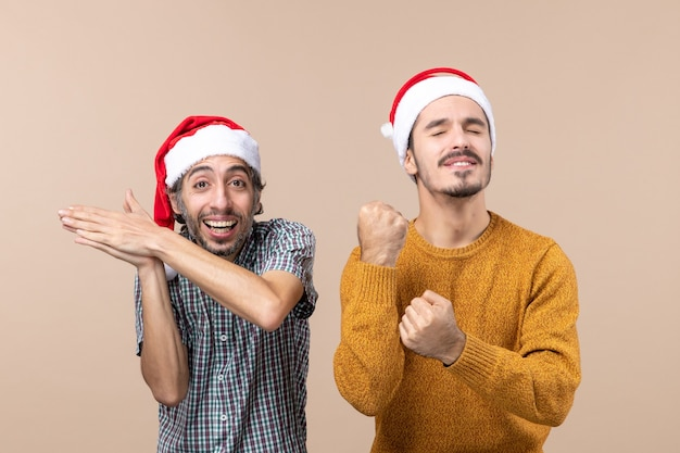 Vista frontal de dois caras com chapéu de papai noel, um batendo palmas e o outro batendo com os olhos fechados em um fundo bege isolado