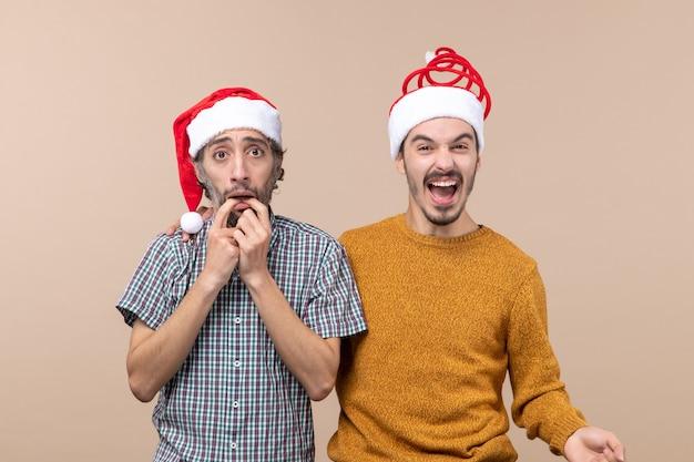 Vista frontal de dois caras com chapéu de papai noel, um deprimente e o outro rindo em um fundo bege isolado