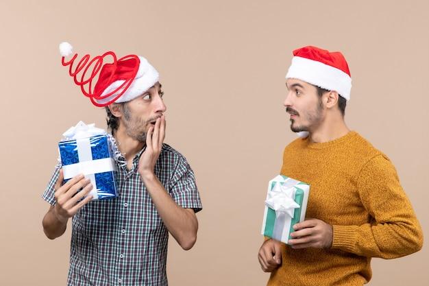 Vista frontal de dois caras confusos com chapéu de papai noel segurando presentes de natal, compartilhando segredos em um fundo bege isolado