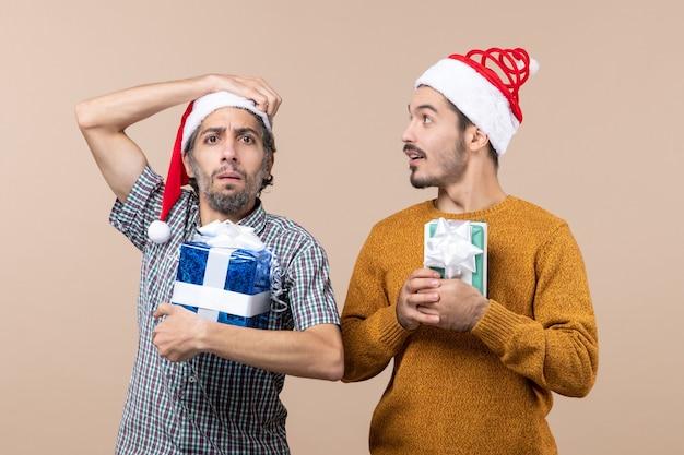 Vista frontal de dois caras confusos com chapéu de papai noel segurando presentes de natal e um coçando a cabeça em um fundo bege isolado
