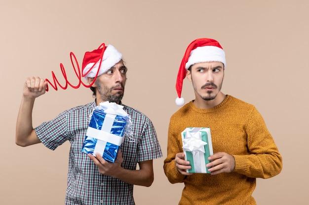 Vista frontal de dois caras confusos com chapéus de papai noel e presentes de natal tentando se concentrar em um fundo bege isolado