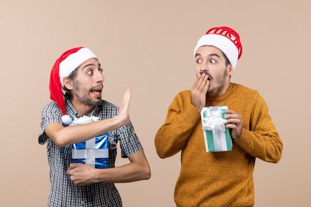 Vista frontal de dois caras confusos compartilhando segredo e segurando presentes de natal em um fundo bege isolado