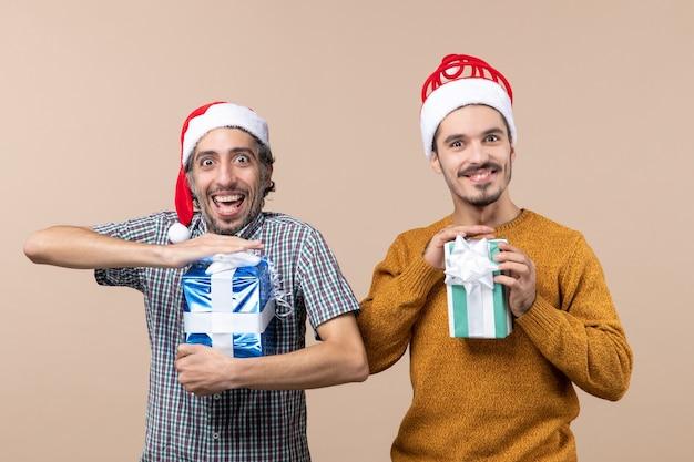 Vista frontal de dois caras confusos curtindo e segurando os presentes de natal em um fundo bege isolado