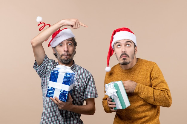 Vista frontal de dois caras confusos segurando o natal e apresentando a ponta de um dedo mostrando o outro em um fundo bege isolado