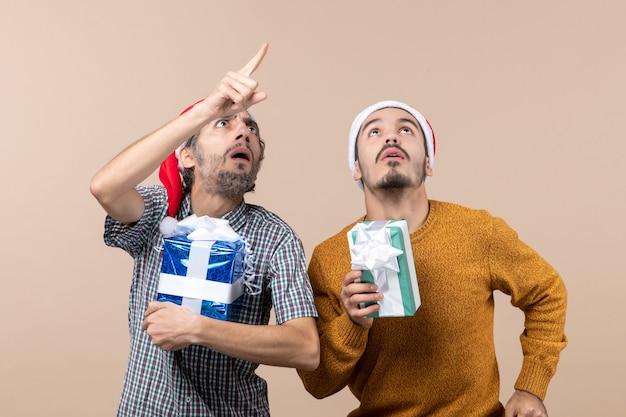 Vista frontal de dois caras confusos segurando presentes de natal e olhando para o alto em um fundo bege isolado
