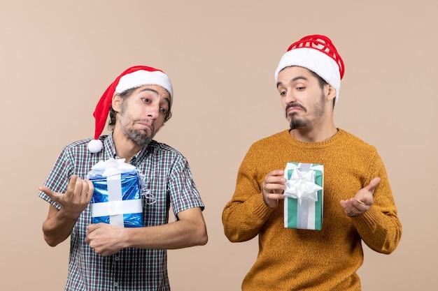 Vista frontal de dois caras confusos segurando presentes de natal em um fundo bege isolado
