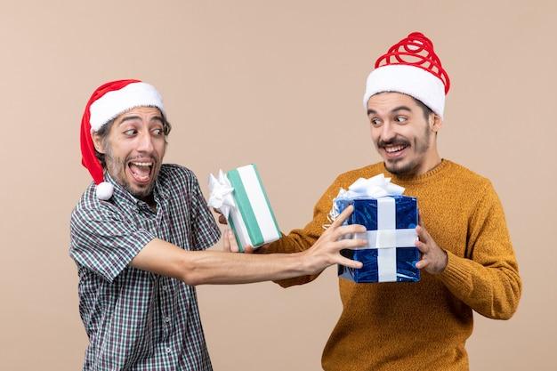 Vista frontal de dois caras confusos trocando seus presentes de natal em um fundo bege isolado