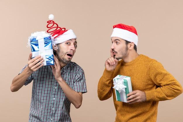 Vista frontal de dois caras confusos, um verificando seus presentes de natal e o outro fazendo sinal shh em fundo bege isolado