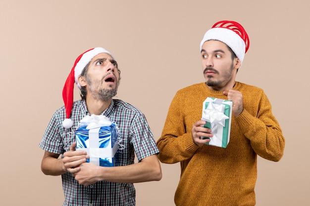 Vista frontal de dois caras confusos usando chapéus de papai noel e segurando presentes de natal em um fundo bege isolado