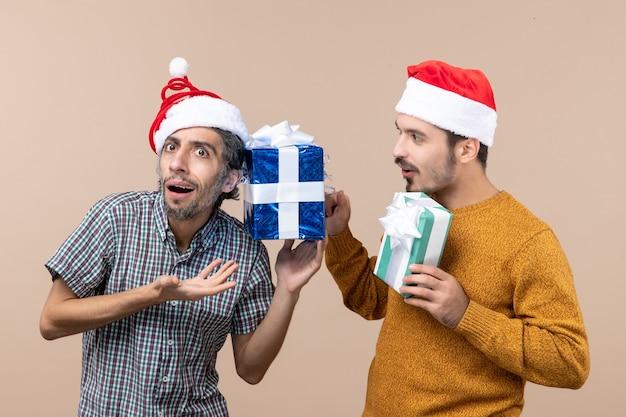Vista frontal de dois caras confusos usando chapéus de papai noel e verificando seus presentes de natal em um fundo bege isolado
