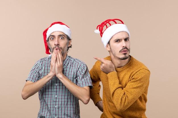 Vista frontal de dois caras curiosos com chapéu de papai noel, um colocando a mão em seu queixo e o outro apontando o dedo mostrando seu amigo em um fundo bege isolado