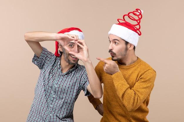 Vista frontal de dois caras de natal com chapéu de papai noel, um fazendo formato de coração com as mãos em fundo bege isolado