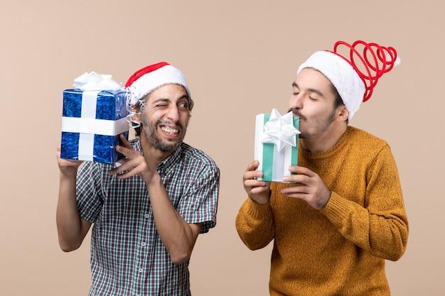 Vista frontal de dois caras felizes curtindo seus presentes de natal em um fundo bege isolado