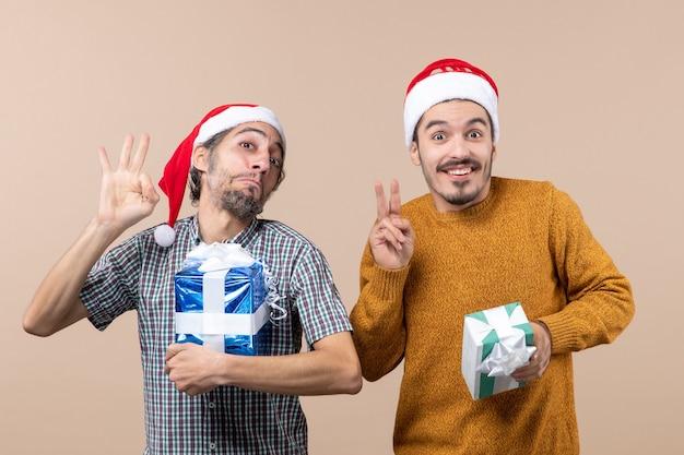 Vista frontal de dois caras felizes, um fazendo sinal de ok e o outro de vitória segurando os presentes de natal em um fundo bege isolado