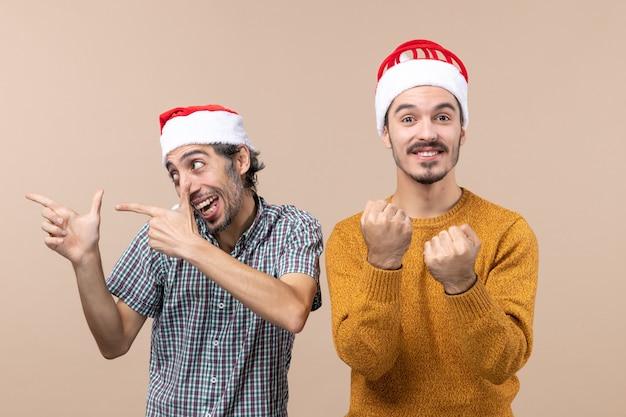 Vista frontal de dois caras maravilhados com chapéu de papai noel, um olhando para a esquerda e o outro socando em um fundo bege isolado