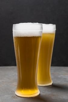 Vista frontal de dois copos com cerveja com espuma