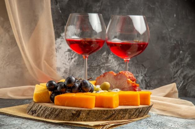 Vista frontal de dois copos de vinho tinto e o melhor lanche com várias frutas e alimentos em uma bandeja de madeira marrom