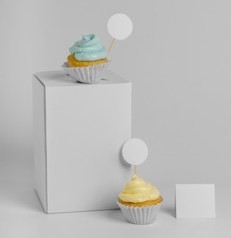 Vista frontal de dois cupcakes com caixa de embalagem