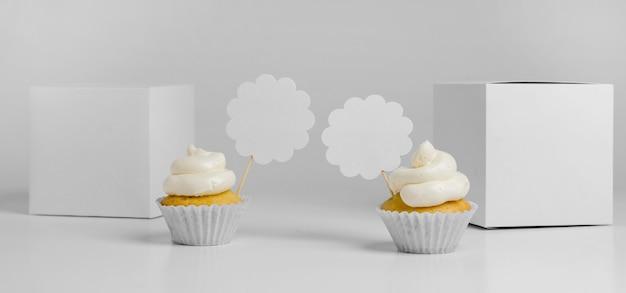 Vista frontal de dois cupcakes com caixas de embalagem