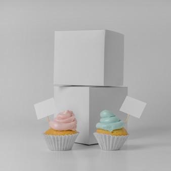 Vista frontal de dois cupcakes com cartões em branco e caixas de embalagem