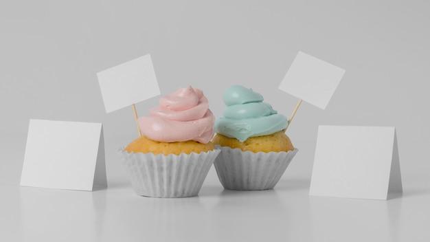 Vista frontal de dois cupcakes com cartões em branco