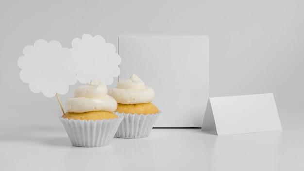 Vista frontal de dois cupcakes com embalagem e espaço de cópia