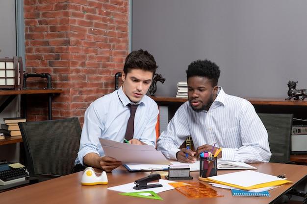 Vista frontal de dois empresários atentos discutindo o projeto