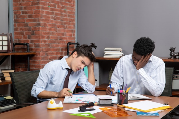 Vista frontal de dois empresários cansados trabalhando juntos