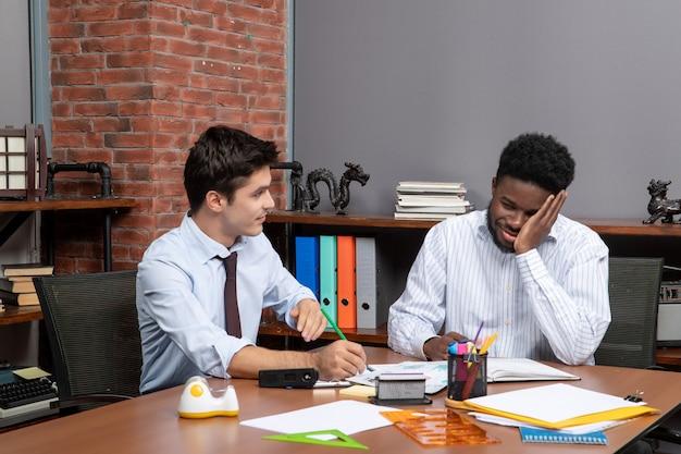 Vista frontal de dois empresários confusos discutindo projeto