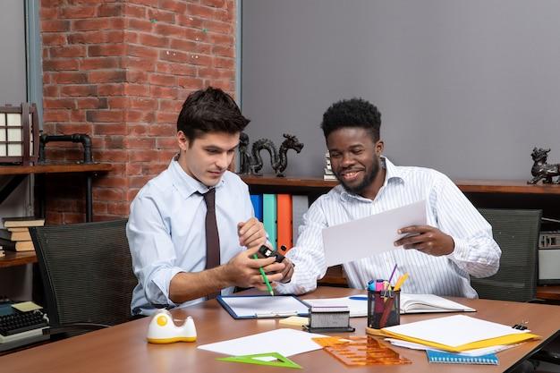 Vista frontal de dois empresários discutindo o projeto enquanto um deles segurando o grampeador